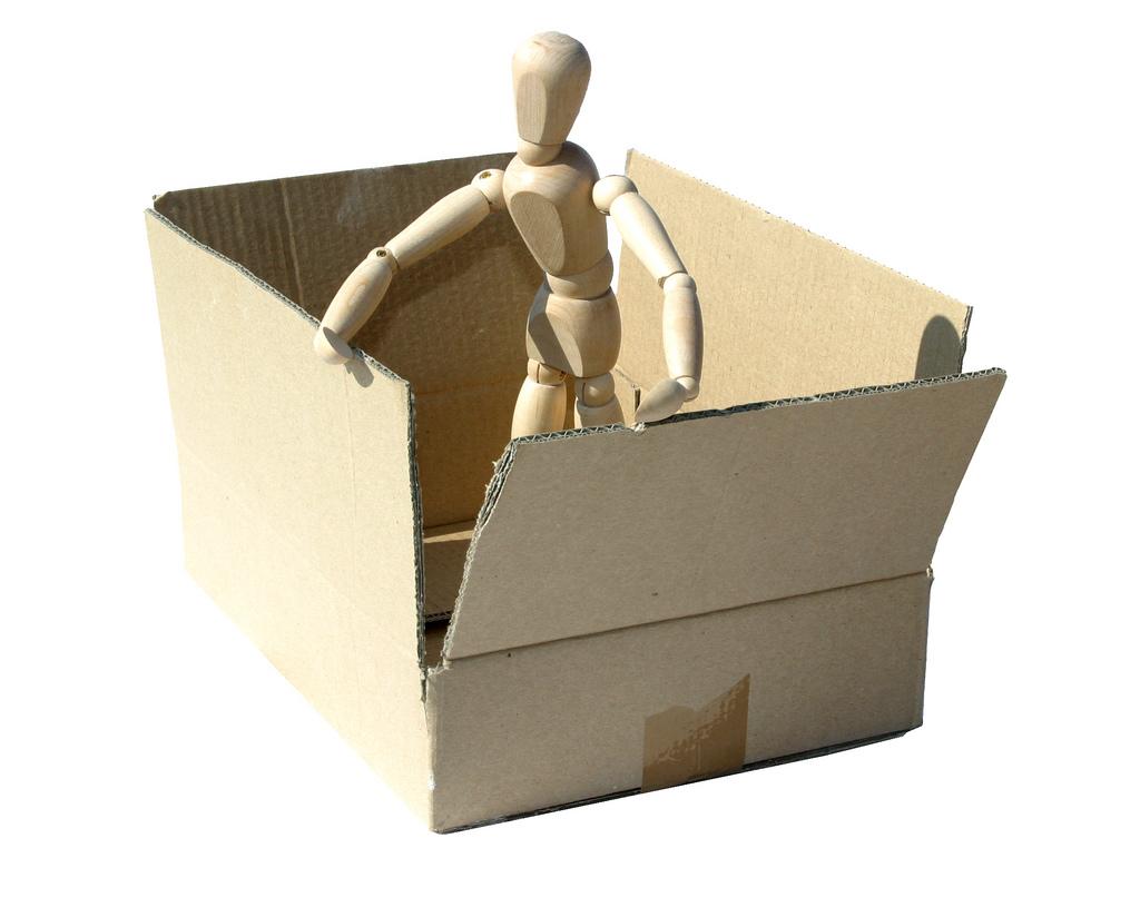 Figur, welche out einem Pappkarton herausklettern will